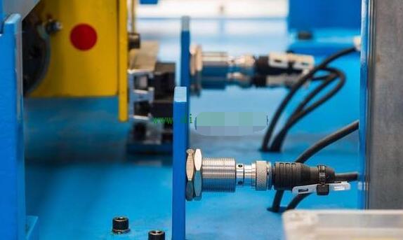 图二接近开关的现场应用   如图二所示,是接近开关在工业现场的实际应用,它一般通过支架固定,当检测物体靠近的时候,它的指示灯会亮,表示接近开关有了输出,同样,如果接线正确,PLC就会有输入信号。接近开关怎样接入PLC的输入点呢?其实它和按钮开关类似,一般接近开关都有三根线,分别是棕色,蓝色和黑色。棕色和蓝色是电源,通常棕色为24V,蓝色为0V。黑色是信号线,接到PLC的输入,而这个信号正是我们所需要的。